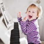 Child laughing at piano.